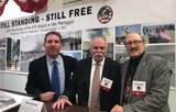 Photo of the 911 Pentagon Still Standing Still Free photographers Sean Kelley, Bob Pugh and Joe Pisciotta standing in front of an exhibit of photos of the Pentagon after the attack.
